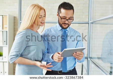Two confident colleagues networking in office - stock photo