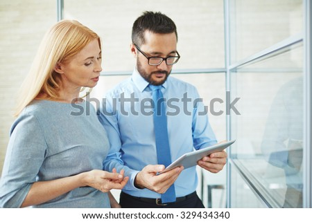 Two confident colleagues with touchpad looking at data at meeting - stock photo