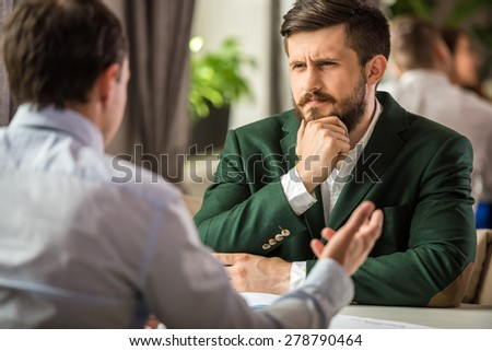 Two confident managers sitting at the table in cafe and discussing project seriously. - stock photo