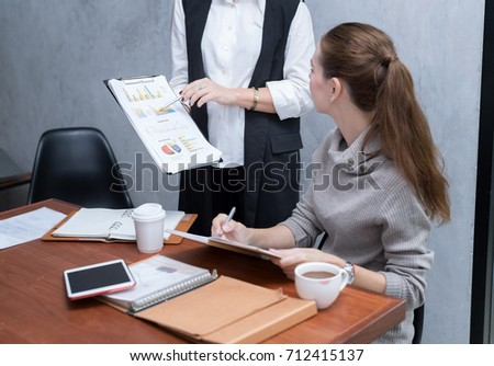 Two confident young business people looking at laptop monitor while their colleagues working in the background. Setup studio shooting.