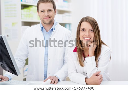 Two confident young pharmacists at work with the man working on the computer as the woman leans forwards over the counter with a smile - stock photo