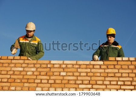 two construction mason worker bricklayer installing red brick with trowel putty knife outdoors - stock photo