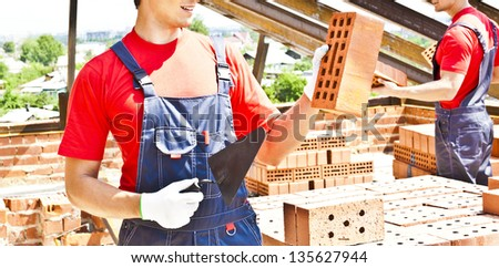 two construction masons workers bricklayer installing red brick with trowel putty knife outdoors - stock photo