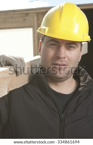 Two construction men working outside building a house with piece of wood.