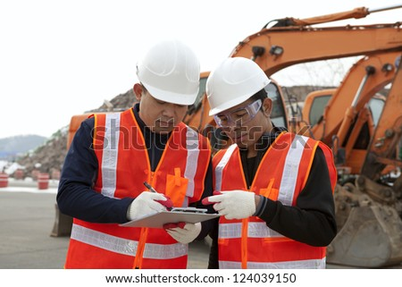 two construction worker discussion on construction site with excavator on the background - stock photo