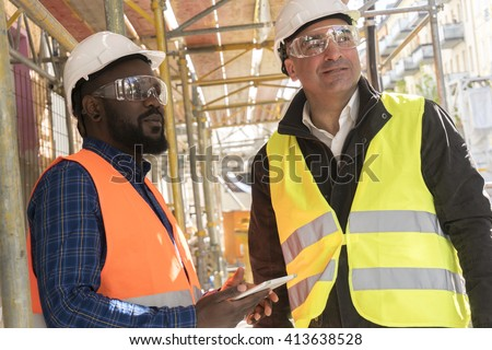 Two construction workers, a black and a white, wearing orange and yellow safety jackets and helmets among scaffolding on construction site - stock photo