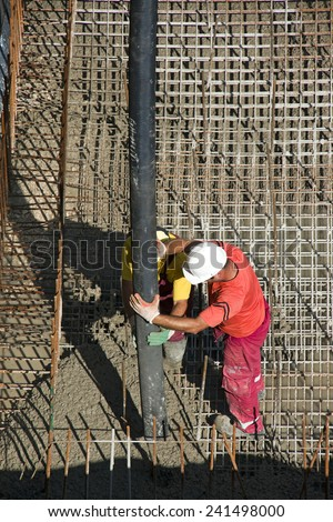 Two construction workers casting foundations of hydro power plant - stock photo