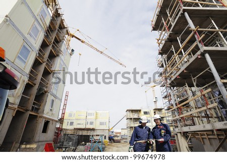 two construction workers inside large building-site, cranes and scaffoldings - stock photo