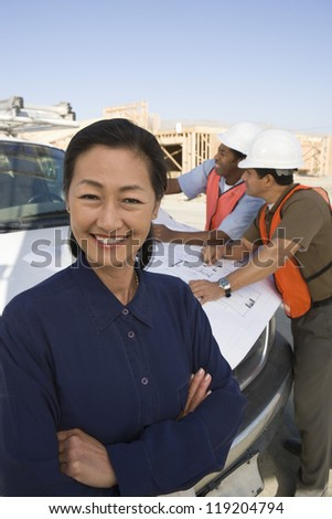 Two construction workers looking at blueprints and architect at construction site - stock photo
