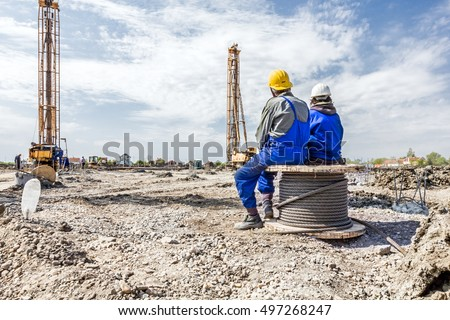 Two construction workers with helmets are sitting on wooden spool with steel cable