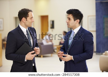 Two Consultants Having Meeting In Hospital Reception