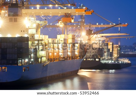 Two container ships being unloaded at the Rotterdam Harbor. A small support vessel is moored off next to the freight carrier in front. - stock photo