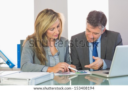 Two content mature business people trying to understand figures at office - stock photo