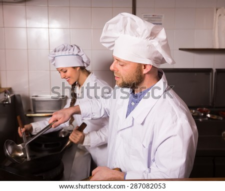 Two cooks working together at kitchen in take-away restaurant