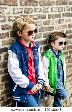 two cool kids with sunglasses looking tough - stock photo