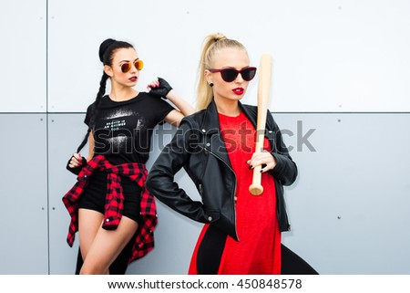Two cool trendy bold girl in black and red casual clothes on a white background, with baseball bat, blonde and brunette wearing sunglasses, shorts, T-shirts, leather jacket. Fashion Beauty Swag Girl. - stock photo
