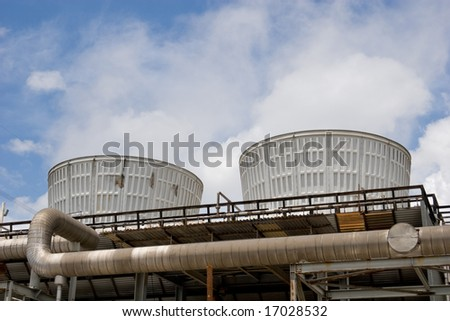 Two cooling towers emitting steam, with a blue sky background