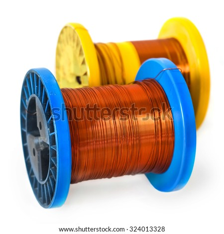 Two Copper wire spools on white background. Yellow ?oil in the background is blurred, soft focus. The wire is partially wound on the yellow coil