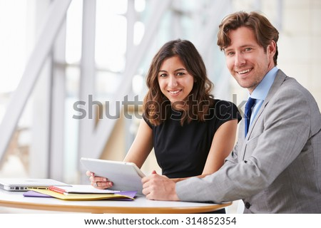 Two corporate business colleagues at work smiling to camera - stock photo