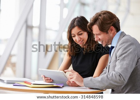 Two corporate business colleagues working together in office - stock photo
