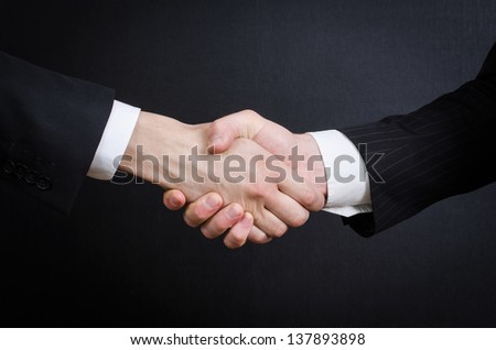 Two corporate hands symbolising the merger - stock photo