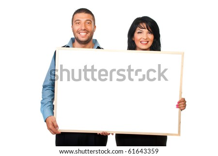 Two corporate people holding and showing a blank banner and laughing together isolated on white background - stock photo