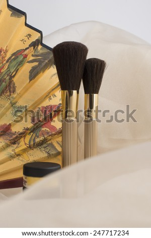 Two cosmetic brushes and two eyeshadow on the beige background - stock photo