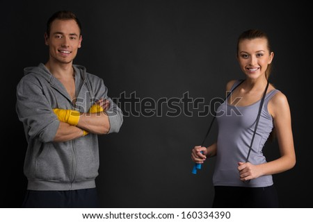 Two couches smiling at camera. Standing isolated on black  - stock photo