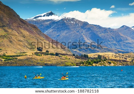 two couple of friends run kayaks a lake with mountain in the background in New Zealand in the Southern Alps. - stock photo