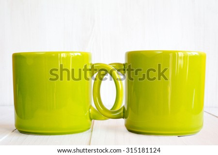Two coupled coffee mugs on wooden background - stock photo