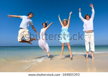 Two couples celebrating on the beach.
