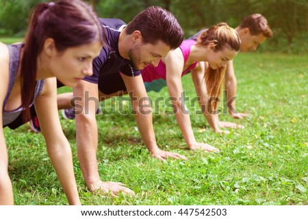 Two couples doing crossfit exercises performing push-ups in the planking position on green grass outdoors in a park