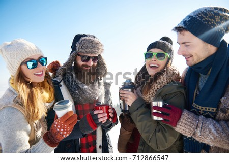 Two couples drinking warm tea from vacuum bottle