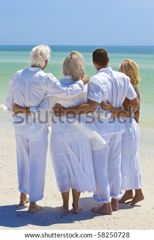 Two couples, generations of a family together embracing arms around each other in a hug on a tropical beach