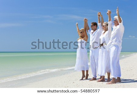 Two couples, generations of a family together holding hands and racing their arms in celebration on a deserted tropical beach