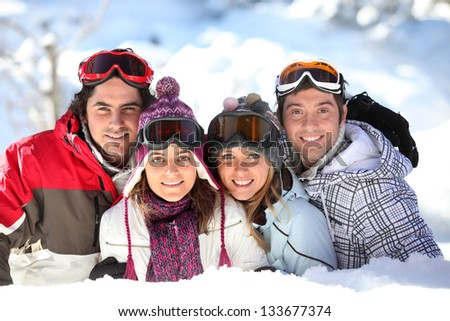 Two couples in a ski slope - stock photo