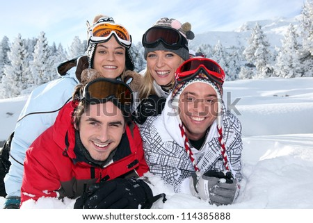 Two couples laying in the snow - stock photo