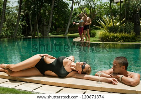 Two couples lounging and relaxing by the edge of a swimming pool in a tropical destination hotel spa garden while on vacations. - stock photo