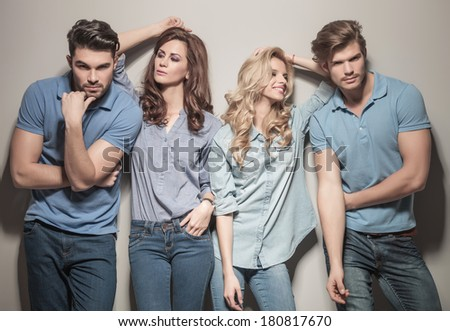 two couples of young casual fashion people posing for the camera, women looking at their men - stock photo