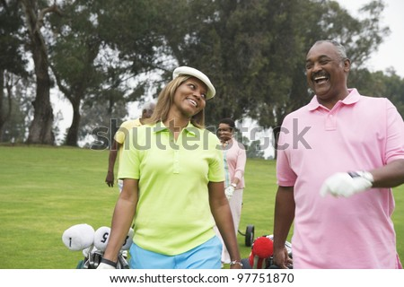 Two couples play golf together - stock photo