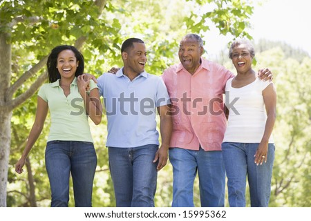 Two couples walking outdoors arm in arm smiling - stock photo