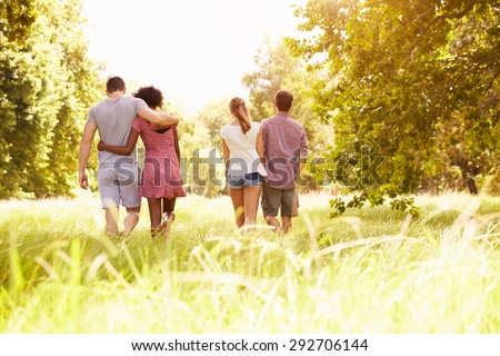 Two couples walking together in the countryside, back view - stock photo