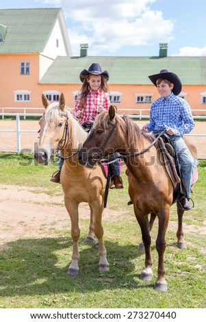two cowboy children on horsebacks - stock photo