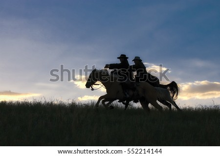 Two cowboys galloping across Montana ridge at dawn