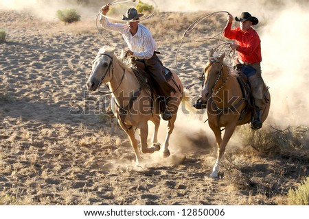 Two Cowboys galloping and roping through the desert - stock photo