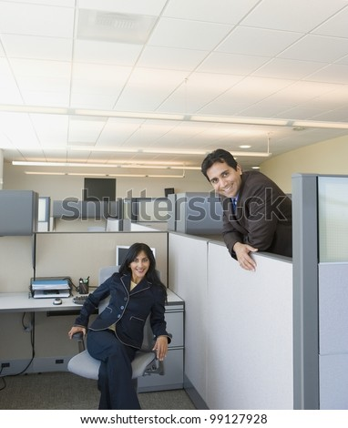 Two coworkers in office cubicles - stock photo