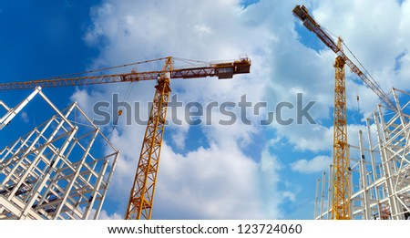 Two cranes build industrial buildings on a background beautiful sky - stock photo