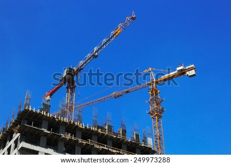 Two cranes on construction site of new office building. - stock photo