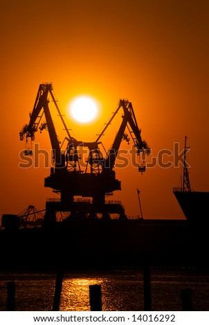 Two cranes sit dramatically against a colorful sunset in a large shipyard