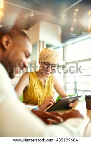 Two creative millenial small business owners working on social media strategy using a digital tablet while sitting at desk - stock photo